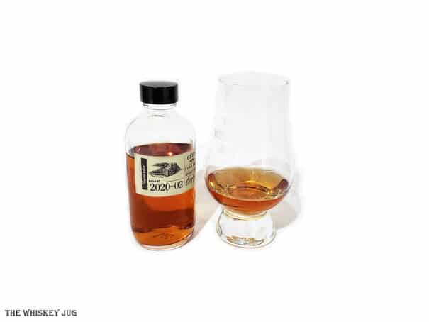 """White background tasting shot with the Booker's Bourbon 2020-02 """"Boston Batch"""" bottle and a glass of whiskey next to it."""