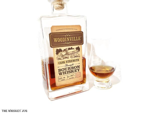 White background tasting shot with the Woodinville Cask Strength Bourbon Whiskey bottle and a glass of whiskey next to it.