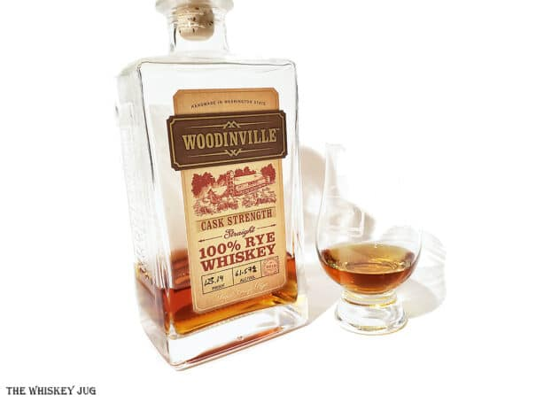 White background tasting shot with the Woodinville Cask Strength Rye Whiskey bottle and a glass of whiskey next to it.