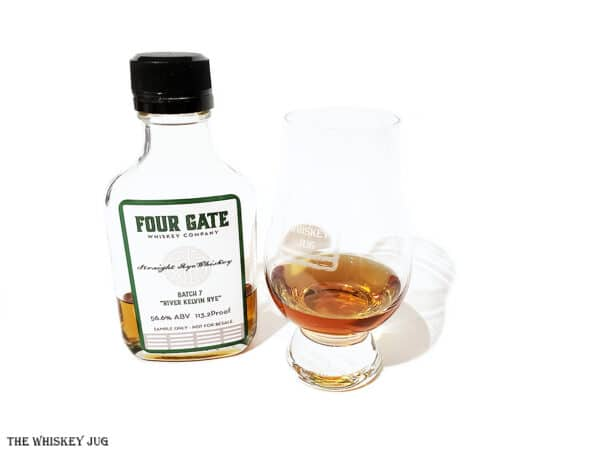 """White background tasting shot with the Four Gate Batch 7 """"River Kelvin Rye""""bottle and a glass of whiskey next to it."""
