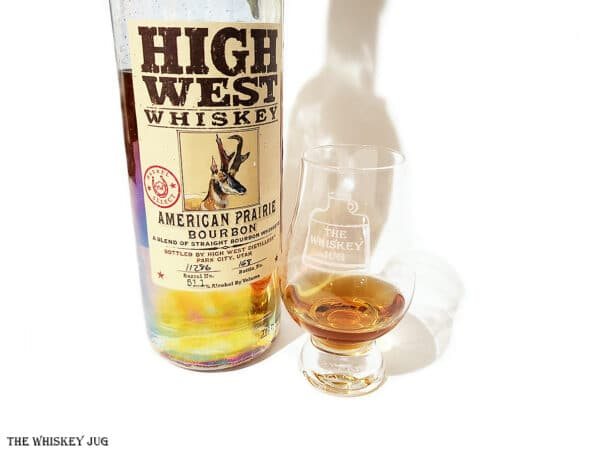 White background tasting shot with the High West American Prairie Bourbon Barrel Selectbottle and a glass of whiskey next to it.