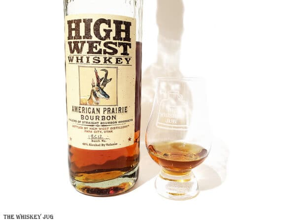 White background tasting shot with the High West American Prairie Bourbonbottle and a glass of whiskey next to it.