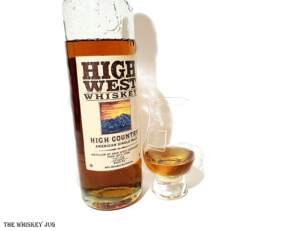 White background tasting shot with the High West High Country Single Malt bottle and a glass of whiskey next to it.