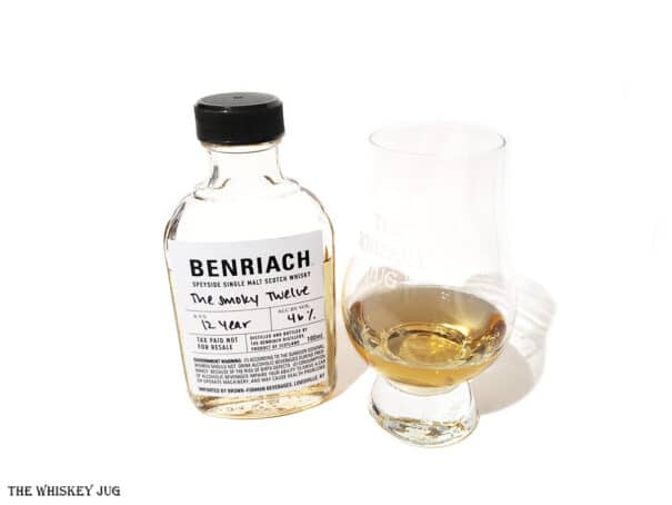 White background tasting shot with the BenRiach Smoky Twelve bottle and a glass of whiskey next to it.