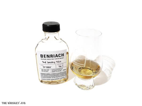 White background tasting shot with the BenRiach The Smoky Ten bottle and a glass of whiskey next to it.