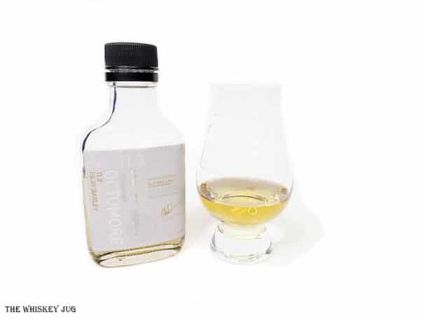 White background tasting shot with the Octomore 11.3 sample bottle and a glass of whiskey next to it.