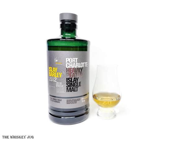 White background tasting shot with the Port Charlotte Islay Barley 2012 bottle and a glass of whiskey next to it.