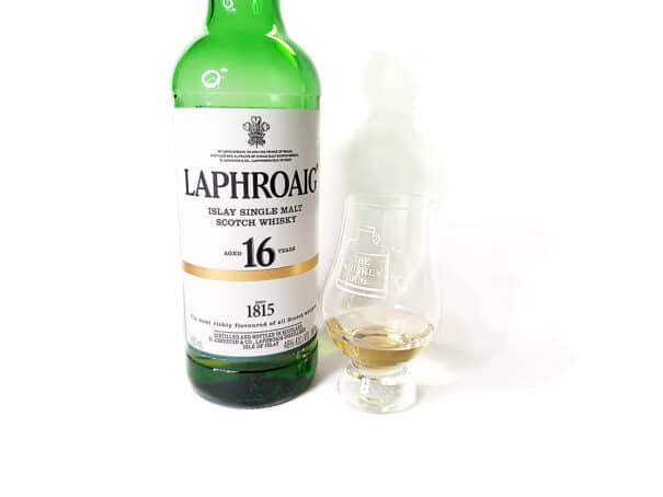 White background tasting shot with the Laphroaig 16 Years Limited Edition bottle and a glass of whiskey next to it.