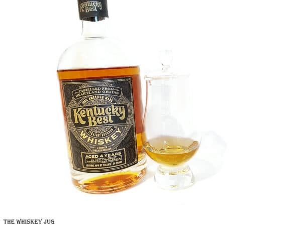 "White background tasting shot with the Trader Joe's ""Kentucky Best"" Bourbon Review bottle and a glass of whiskey next to it."