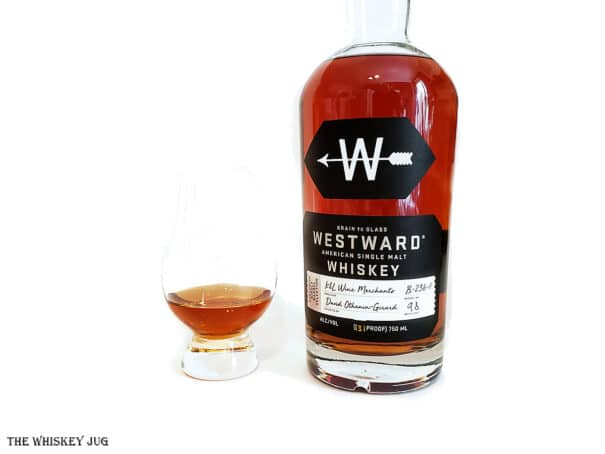 White background tasting shot with the Westward Single Barrel American Single Malt Whiskeybottle and a glass of whiskey next to it.