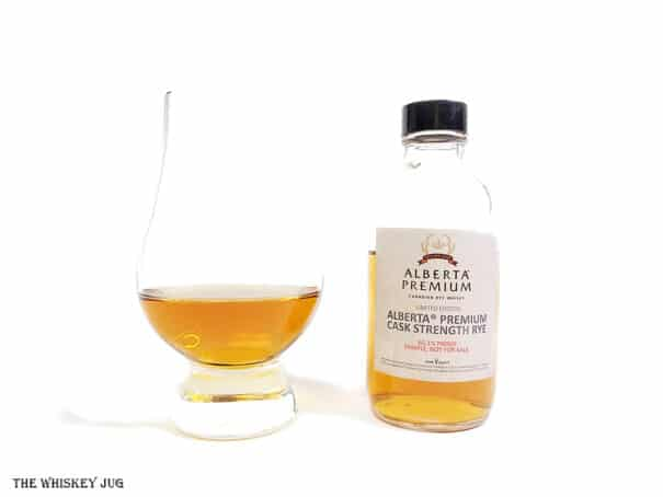 White background tasting shot with the Alberta Premium Cask Strength Rye bottle and a glass of whiskey next to it.